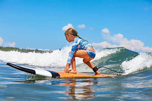 image of a smll girl surfing